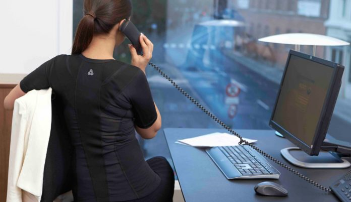 Zu sehen ist eine Frau am Arbeitsplatz - mit smarter Bekleidung.